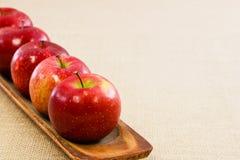 Cinq pommes rouges fraîches ont aligné sur un plateau en bois Photo stock