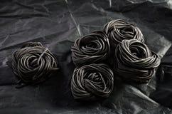 Cinq portions de pâtes noires avec l'encre de seiches sur un backg foncé Photo libre de droits