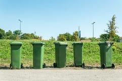 Cinq poubelles industrielles en plastique vertes avec l'ordure et les ordures sur la rue dans le camion de déchargeur de attente  photos libres de droits
