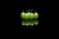 Cinq raisins sur le fond réfléchi noir Photo libre de droits
