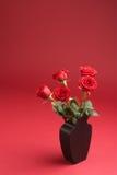 Cinq roses rouges dans le vase sur le fond rouge Images libres de droits