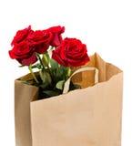 Cinq roses rouges dans un sac de papier sur le fond blanc Image libre de droits