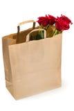 Cinq roses rouges dans un sac de papier sur le fond blanc Photos libres de droits