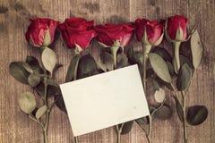 Cinq roses rouges et carte vierge photos stock