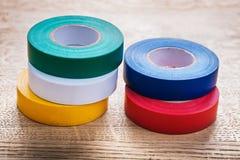 Cinq rouleaux colorés de bande d'isolation sur en bois Photos libres de droits