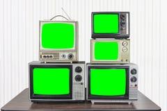 Cinq télévisions de cru avec les écrans verts principaux de chroma photographie stock libre de droits