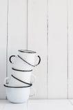 Cinq tasses émaux par blanc Photographie stock libre de droits