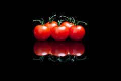 Cinq tomates un fond noir Image stock
