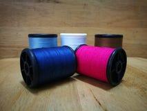 Cinq tubes de fil sont empilés au dos du bois Photo stock