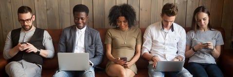 Cinq types divers de filles d'hommes d'affaires s'asseyant sur le divan utilisant des instruments images stock