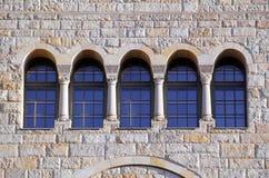 Cinq vieilles fenêtres avec des voûtes, des colonnes et des trellis sur un wa en pierre Image libre de droits