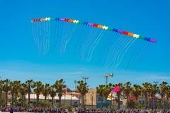 Cinquanta aquiloni che volano insieme in una fila immagine stock