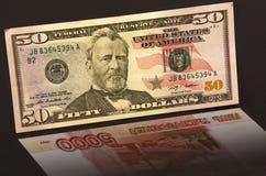 Cinquanta dollari con le rubli russe di riflessione 5.000 Fotografia Stock