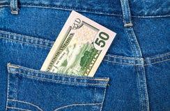 Cinquanta dollari di fattura che attacca dalla tasca dei jeans Fotografia Stock
