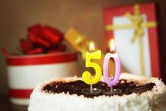 Cinquante ans d'anniversaire Gâteau avec les bougies et les cadeaux brûlants Photographie stock