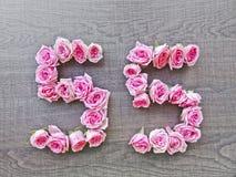 55, cinquante-cinq - nombre de cru de roses roses sur le fond de wood5 foncé photographie stock
