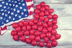 Cinquante coeurs en plastique rouges et drapeau américain sur une surface en bois Image libre de droits