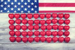 Cinquante coeurs rouges dans une rangée et un drapeau américain Image libre de droits