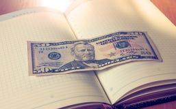 Cinquante dollars et blocs-notes américains sur la table en bois Image stock