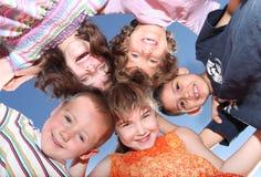 Cinque amici all'aperto che osservano giù sorridere Immagine Stock