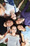 Cinque amici allegri che si trovano sul ritratto di punto di vista superiore dell'erba Fotografie Stock