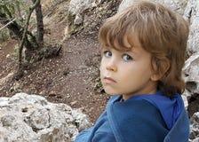 Cinque anni del ragazzo, sguardo infelice, occhi azzurri, sedersi all'aperto sulla roccia Fotografie Stock Libere da Diritti