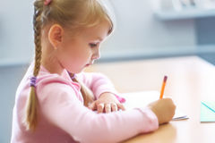 Cinque anni della ragazza bionda che si siede all'aula ed alla scrittura Immagine Stock