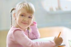 Cinque anni della ragazza bionda che si siede all'aula ed alla scrittura Fotografia Stock