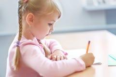 Cinque anni della ragazza bionda che si siede all'aula ed alla scrittura Immagini Stock Libere da Diritti