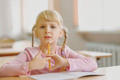Cinque anni della ragazza bionda che si siede all'aula ed alla scrittura Fotografie Stock Libere da Diritti