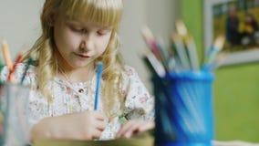 Cinque anni di ragazza bionda disegna Nella priorità alta, un vaso con le matite stock footage