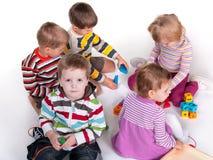 Cinque bambini che giocano i giocattoli variopinti Fotografia Stock