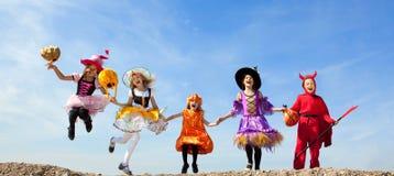 Cinque bambini di Halloween che saltano al cielo blu Fotografia Stock Libera da Diritti