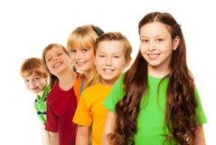 Cinque bambini felici che si levano in piedi in una riga Fotografie Stock Libere da Diritti