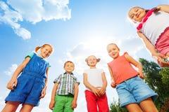 Cinque bambini graziosi che esaminano giù la macchina fotografica Fotografie Stock Libere da Diritti