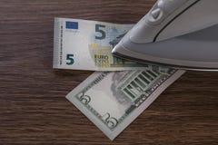 Cinque banconote dell'cinque-euro e del dollaro sotto il ferro sulla tavola di legno fotografia stock
