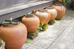 Cinque barattoli arancio antichi sono sistemati insieme Fotografia Stock Libera da Diritti