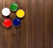 Cinque barattoli con delle le pitture colorate multi stanno su una tavola di legno, Fotografia Stock Libera da Diritti