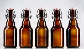 Cinque bottiglie di vetro in bianco di birra Immagine Stock