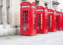 Cinque cabine telefoniche rosse tutte di Londra in una fila Fotografia Stock