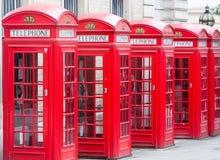 Cinque cabine telefoniche rosse tutte di Londra in una fila Fotografia Stock Libera da Diritti