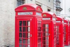 Cinque cabine telefoniche rosse tutte di Londra in una fila Fotografie Stock Libere da Diritti