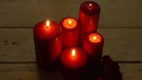 Cinque candele rosse accendono la fiamma sulla tavola di legno bianca, tema romantico