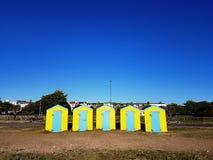 Cinque case di spiaggia chiuse sulla riva di mare sabbiosa fotografia stock libera da diritti