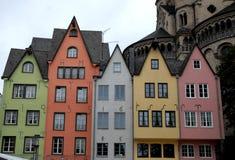 Cinque case variopinte e una grande torre nel centro di Colonia in Germania Immagini Stock Libere da Diritti