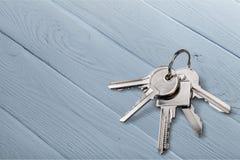 Cinque chiavi della casa su fondo di legno fotografia stock