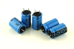 Cinque condensatori elettrolitici in blu Fotografie Stock Libere da Diritti