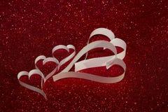 Cinque cuori bianchi da carta su fondo brillante rosso Fotografia Stock