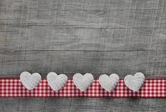 Cinque cuori bianchi su un vecchio fondo di legno grigio con un checke Fotografia Stock
