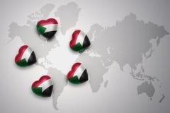 Cinque cuori con la bandiera nazionale del Sudan su un fondo della mappa di mondo Fotografia Stock Libera da Diritti